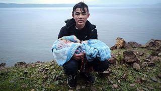 Ege Denizi'ni sandalla geçtikten sonra Yunanistan'ın Midilli adasına bağlı Skala Sikaminias köyüne yürürken kucağındaki bebekle yol kenarında dinlenen bir göçmen