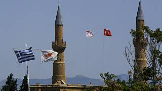 Greek, left, and Cyprus' flags, second left, flutter on poles in the south, as in the north Turkish occupied area, a Turkish & Turkish Cypriot breakaway flags fly on a minaret
