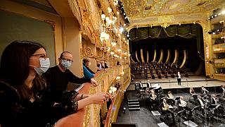 """Spectators attend the performance of """"Verdi e la Fenice"""" to mark the reopening of the Fenice Opera theatre in Venice."""