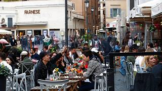 People sit at a cafe restaurant in Rome, Monday, April 26, 2021.