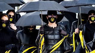 Women wearing black clothing and face masks with radioactivity sign march under umbrellas in Minsk. April 26, 2021