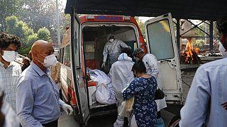 Profissionais de saúde transferem corpos de uma ambulância para um crematório em Nova Deli