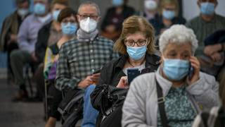 People wait after receiving the AstraZeneca vaccine at a temporally vaccination centre at the Fira of Barcelona, Spain, Monday, April 26, 2021.
