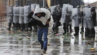 Un hombre huye de la policía tras lanzarle piedras durante una protesta en Colombia