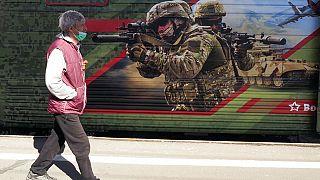 Мужчина в маске проходит мимо графити.