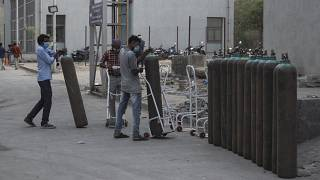 Workers stack empty oxygen cylinders near an oxygen plant at a government COVID-19 hospital in Ahmedabad.
