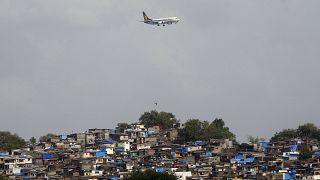 طائرة تحلق فوق الأكواخ المجاورة لمطار تشاتراباتي شيفاجي بينما تستعد للهبوط في مومباي، الهند.