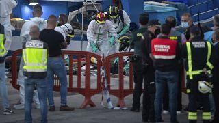 منتسبو خدمات الطوارئ يحملون جثث مهاجرين  بعد وصولهم إلى ميناء لوس كريستيانوس جنوب تينيريفي ، في جزيرة الكناري ، إسبانيا ، الأربعاء 28 أبريل 2021.