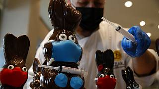 Tassos Vazakas, owner of a cake shop, prepares chocolate bunnies with masks and a vaccination syringe during Holy Week in Athens,
