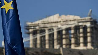 European Union flag is seen in front of the ancient parthenon temple at the Acropolis hill in Athens