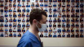 A member of staff passes in front of a collection of portraits of medical staff at Bichat Hospital, AP-HP, in Paris, Thursday, April 22, 2021.