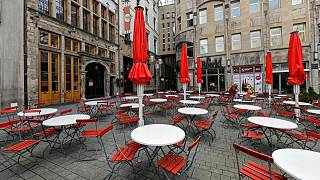 Empty tables are seen on a deserted square in the normally very busy old town of Cologne, Germany, Thursday, March 18, 2021.