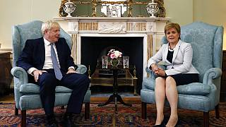 In this Monday. July 29, 2019 file photo, Scotland's First Minister Nicola Sturgeon, right, sits with Britain's Prime Minister Boris Johnson, in Bute House, ahead of their mee