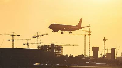 A jet lands at London City Airport at sunset.