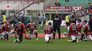 """لاعبو إيه سي ميلان يرتدون قمصانًا تحمل عبارة """"إيه سي ميلان ضد العنصرية"""" أثناء استعدادهم لبدء مباراة كرة القدم في دوري الدرجة الأولى الإيطالي"""