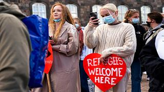 People attend a demonstration against the tightening of Denmark's migration policy and the deportation orders in Copenhagen, Denmark, Wednesday, April 21, 2021.