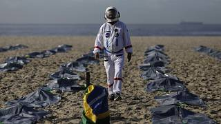 Tercio Galdino walks amid mock body bags representing COVID-19 victims on Copacabana beach.