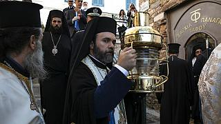 Greek Orthodox Archimandrite Damianos, center, arrives at the church of Agioi Anargyroi holding a cauldron with Holy Fire