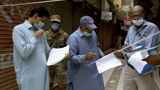 Officials gather to seal a market on the violation of new restrictions announced by government to control the spread of the coronavirus, in Karachi, Pakistan, Saturday.