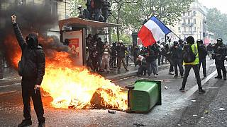 Protesters stand near a burning trash bin in the street during the annual May Day (Labour Day) rally in Paris on May 1, 2021.
