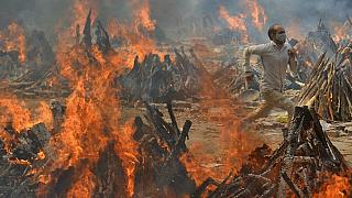A man runs to escape heat emitting from the multiple funeral pyres of COVID-19 victims at a crematorium in the outskirts of New Delhi, India, Thursday, April 29, 2021.