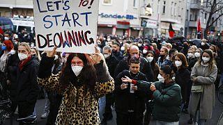 A tulajdon túlzott koncentrációja elleni táblát emel magasba egy tüntető, Berlin, 2021. május 1.