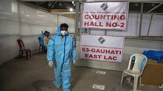 A counting agent in protective suit walks past officials during the counting of votes of Assam state assembly election in Gauhati, India, Sunday, May 2, 2021.