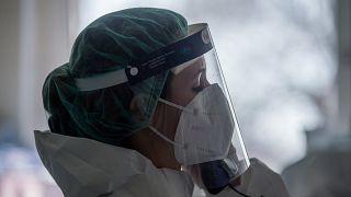 Védőfelszerelést viselő orvos telefonál a fővárosi Honvédkórház koronavírussal fertőzött betegek fogadására kialakított intenzív osztályán 2021. április 1-jén.