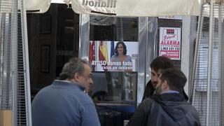 People sit outside a bar with a poster of the president of the Madrid autonomous government, Isabel Diaz Ayuso, on March 22, 2021.