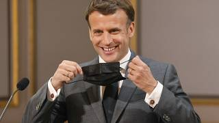 French President Emmanuel Macron removing his protective face mask before delivering a speech