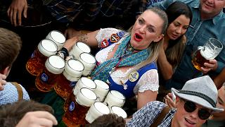 In this Saturday, Sept. 21, 2019 file photo, a waitress holds twelve glasses of beer during the opening of the 186th 'Oktoberfest' beer festival in Munich, Germany