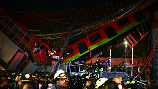 Rescue workers gather at the site of a metro train accident after an overpass for a metro partially collapsed in Mexico City on May 3, 2021.