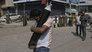 رجل يحمل اسطوانة أكسيجين ليملأها فيما مصابون بكوفيدـ19 ينتظرون في طابور في نيودلهي. 2021/05/03