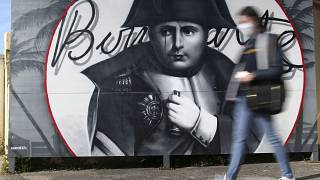 A woman walks past a picture of Napoleon Bonaparte in Corsica ahead of the bicentennial of his death.