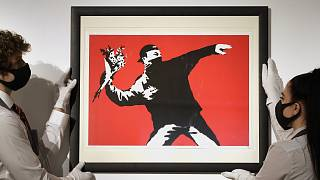 "Gallery technicians display a Banksy artwork called ""Love is in the Air"" read for auction."