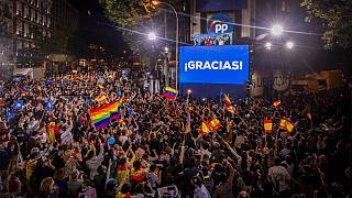 People gather outside the conservative Popular Party's regional headquarters in Madrid, Spain