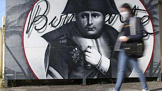 Una donna passeggia di fronte a un murale di Napoleone in Corsica
