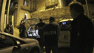 ضباط وعناصر الشرطة يقفون خارج منزل المشتبه به أثناء عملية في سينوبولي، جنوب إيطاليا.