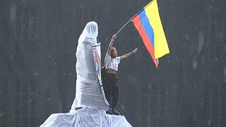 Un chica ondea una bandera de colombia subida en una estatua en el inicio del paro nacional de este miércoles 5 de mayo de 2021