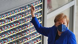 Angela Merkel nimmt ihre Wahlkarte für die Abstimmung im Bundestag