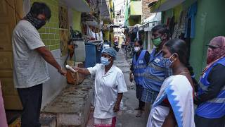 An Indian health worker checks body temperature of a man during a door-to-door survey being conducted as a precaution against COVID-19 in Hyderabad, India, May 6, 2021