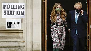 Prime Minister Boris Johnson leaves a polling station with his partner Carrie Symonds