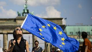 FILE: A woman holds a European flag as she attends a demonstration in Berlin, Germany, Sunday, May 19, 2019.