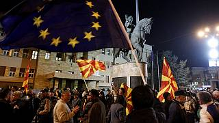 People waving national and EU flags gather for a rally in Skopje, North Macedonia