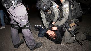 عناصر من الشرطة الإسرائيلية تعتقل شابا فلسطينيا وتطرحه أرضا خلال احتجاجات على تشريد عائلات مقدسية بحي الشيخ جراح. 06/05/2021