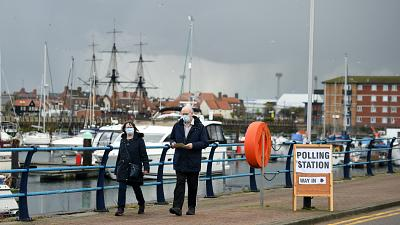 A couple walks past a sign for a Polling Station beside the marina in Hartlepool, north-east England on May 6, 2021