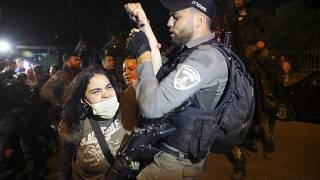A Palestinian woman scuffles with Israeli border police officer during a protest against the planned evictions of Palestinian families in the Sheikh Jarrah