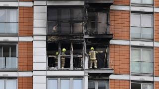 Firefighters are seen at work in a burned flat at the residential tower block in east London.
