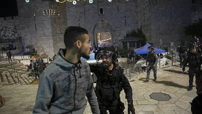 An Israeli policeman shouts at a Palestinian man to leave the Damascus Gate to the Old City of Jerusalem after clashes at the Al-Aqsa Mosque compound, Friday, May 7, 2021.