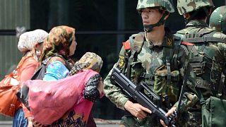 Doğu Türkistan'ın başkenti Urumçi'de Çinli paramiliter güçler ve buradan geçen Uygur kadınlar (arşiv)